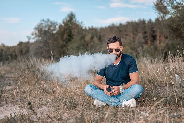 Homme vapotant une cigarette électronique