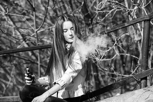 Jeune femme vapotant dans la nature